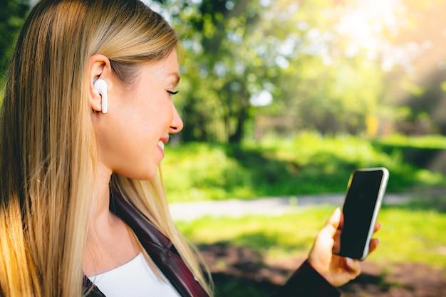 Giovane bella ragazza caucasica adulta sorridente che cammina all'aperto nel parco che ha comunicazione di chat con le cuffie senza fili