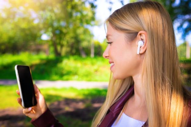 Giovane bella ragazza caucasica adulta sorridente che cammina all'aperto nel parco che ha chat