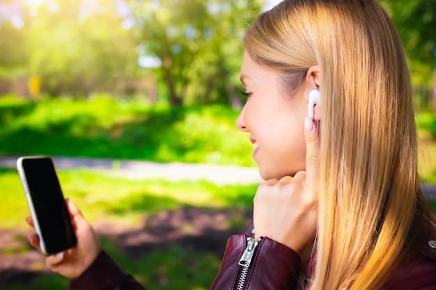 Giovane bella ragazza caucasica adulta sorridente che cammina all'aperto nel parco