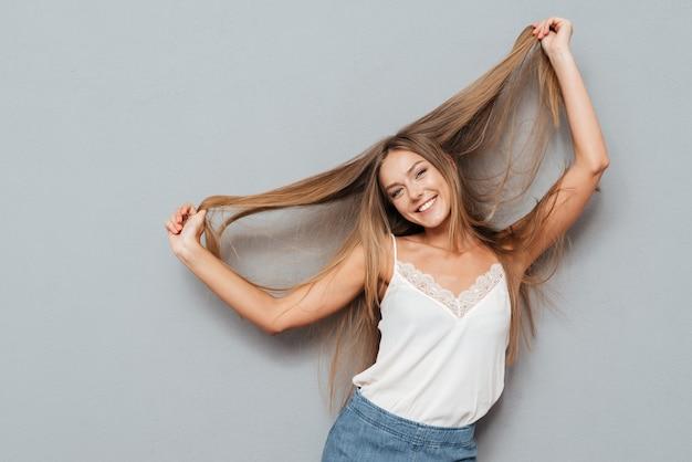 Giovane bella ragazza bionda sorridente con i capelli lunghi in posa isolata su uno sfondo grigio