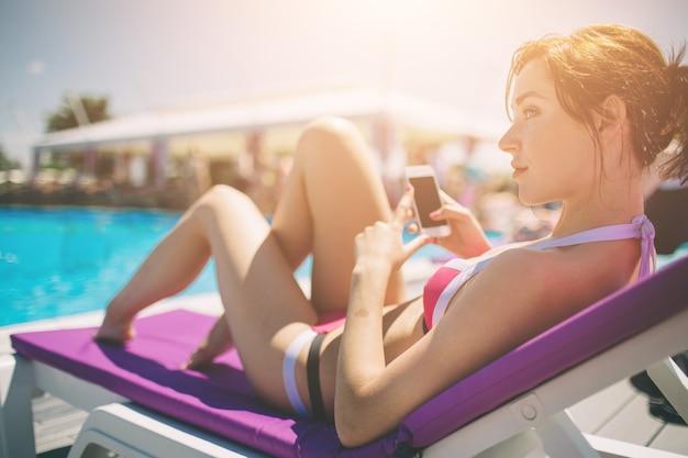 Giovane bella donna sorridente in bikini in piscina calda sulla località e parlare nel telefono cellulare.