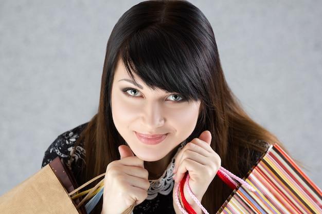 Giovane bella donna sorridente che tiene i sacchetti di carta con gli acquisti. vendita e concetto di acquisto Foto Premium