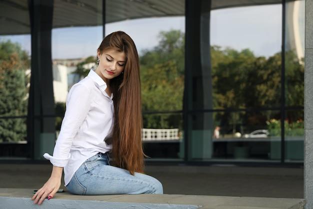Giovane bella donna sorridente con lunghi capelli lisci guardava in basso