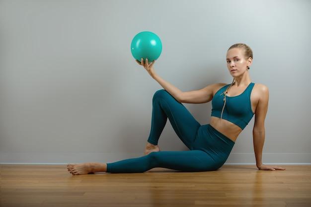 La giovane, bella ragazza sportiva che fa esercizi su un fitball in palestra su sfondo grigio.