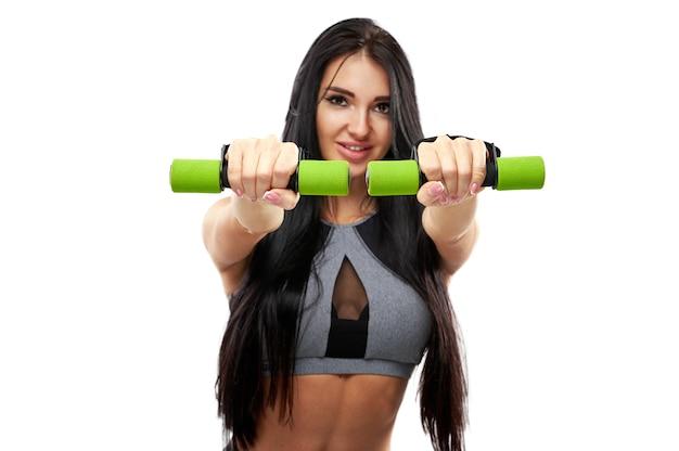 La giovane bella sportiva tiene fuori i manubri sulla macchina fotografica. ritratto isolato su uno sfondo bianco