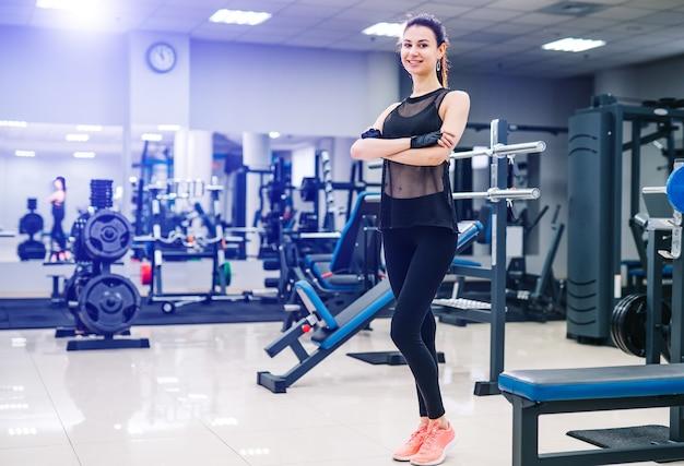 Giovane bella sportiva con bel corpo. ragazza bruna fitness sta con le mani incrociate.