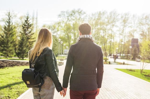 Giovane bella coppia elegante innamorata che si tiene per mano per strada, vista posteriore