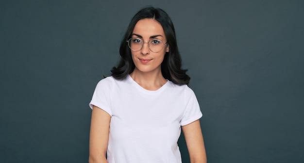 La giovane bella donna felice ed elegante in una maglietta bianca e occhiali da vista sta posando sullo sfondo grigio