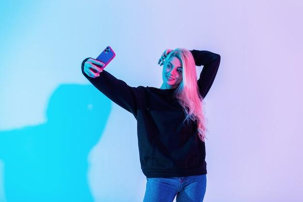 Modello di giovane bella donna alla moda in una felpa con cappuccio nera di moda con jeans blu con un telefono fa una foto selfie in uno sfondo rosa neon in studio