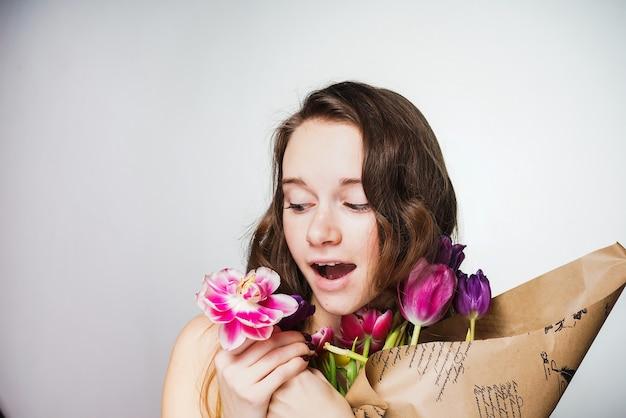 Giovane bella donna sorpresa che tiene un mazzo di fiori, celebrando la giornata mondiale della donna l'8 marzo march