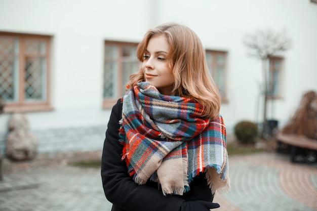 Giovane bella donna dolce in un caldo cappotto invernale alla moda con un'elegante sciarpa a scacchi di lana si trova in una calda giornata autunnale