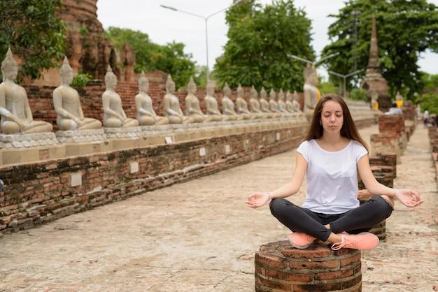 Giovane bella donna turistica che ha vacanza in ayutthaya, tailandese