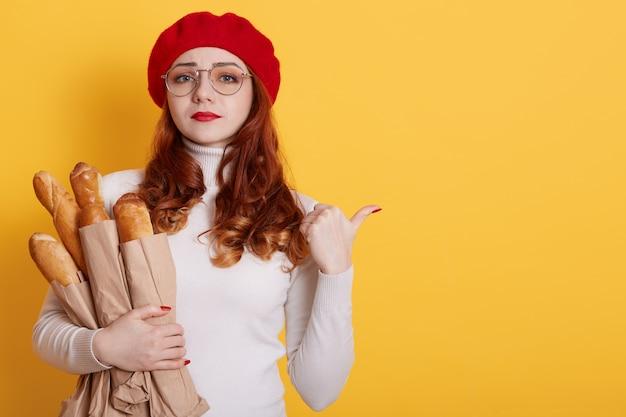 Giovane bella donna sconvolta che tiene il sacchetto di pane sano fresco su colore giallo