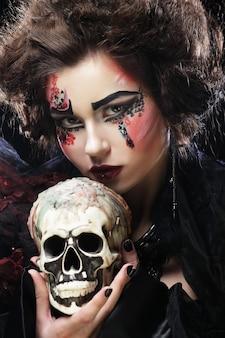 Giovane bella strega che tiene un teschio su sfondo scuro