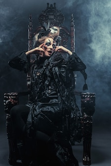 La giovane bella strega si siede su una sedia. trucco luminoso, teschio, tema fumo-halloween.