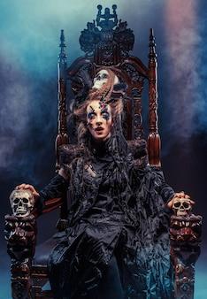 La giovane bella strega si siede su una sedia