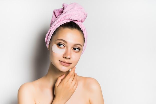 Giovane bella donna dopo il bagno con un asciugamano in testa, cura della pelle, guardando con interesse a sinistra