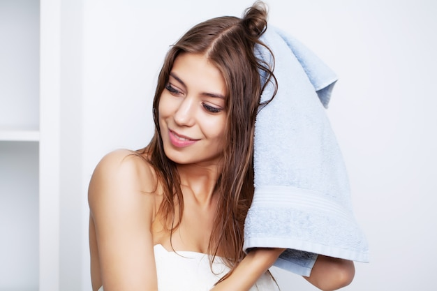La giovane bella donna dopo i trattamenti della stazione termale per cura dei capelli pulisce i capelli con un asciugamano