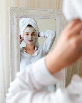 Giovane bella donna applica la maschera per il viso in camera da letto