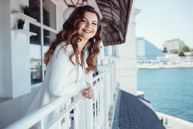 Giovane bella donna su un balcone caffè. aspettando un incontro di lavoro