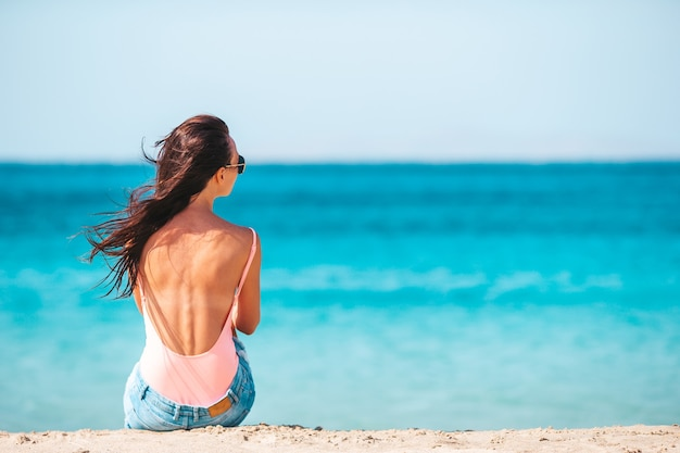 Giovane bella donna sulla spiaggia durante le vacanze estive tropicali