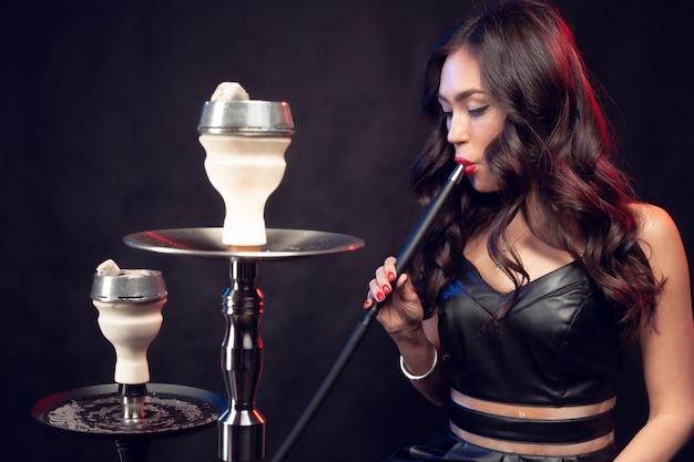 La giovane bella donna in vestito nero che fuma ed espira il narghilé