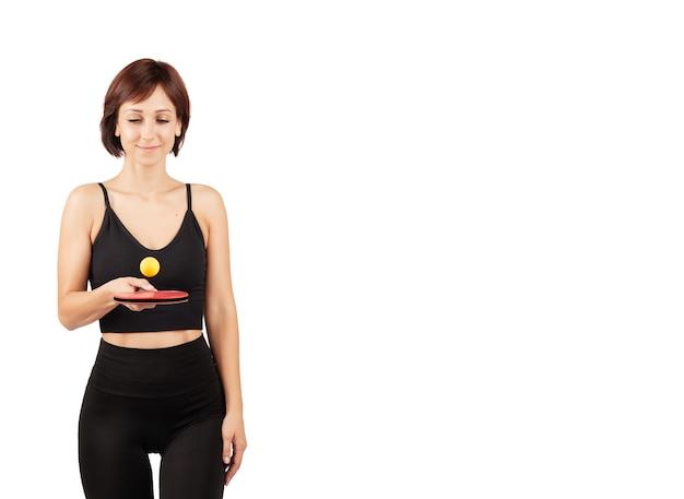 Giovane bella donna in leggings neri e top facendo sport e yoga al chiuso
