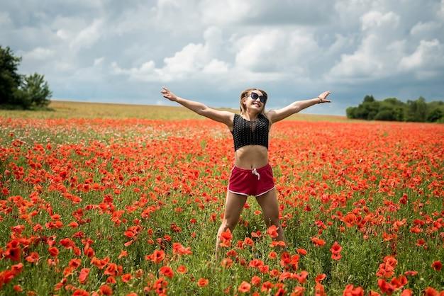 Giovane bella donna in un top nero e pantaloncini rossi corti che salta al campo di papaveri