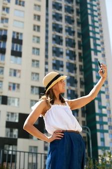 Giovane bella donna blogger in abiti estivi che fa selfie davanti a un edificio moderno
