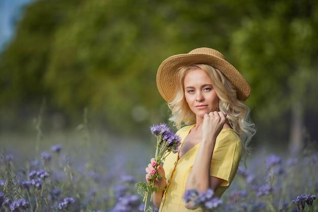 Giovane bella donna bionda in un cappello cammina attraverso un campo di fiori viola. estate. primavera.