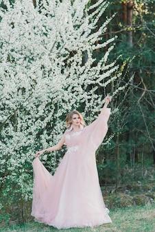 Giovane bella donna nel giardino fiorito. sposa in abito da sposa
