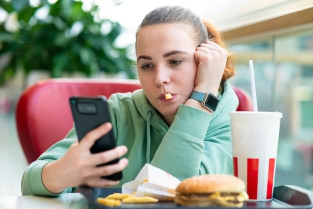 Giovane bella donna annoiata ragazza che mangia cibo spazzatura veloce hamburger hamburger patate patatine fritte e soda