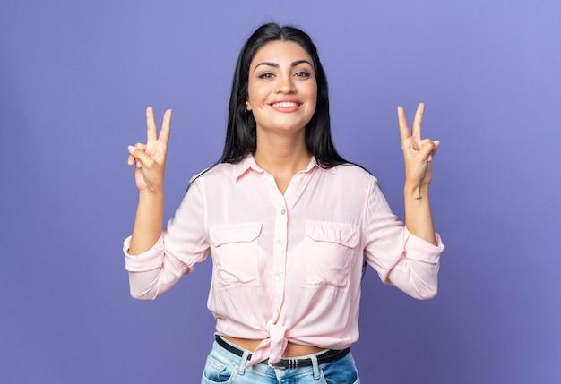 Giovane bella donna in abiti casual felice e positiva che mostra il segno a v che sorride allegramente in piedi sul blu