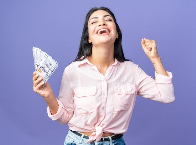 Giovane bella donna in abiti casual in possesso di contanti felice ed eccitata pugno serrato esultando per il suo successo in piedi sul muro blu
