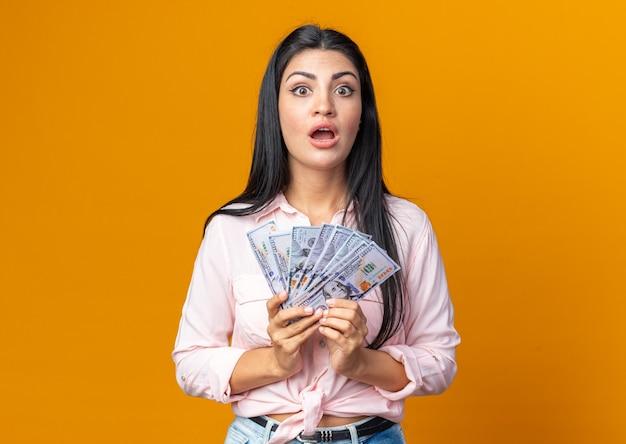 Giovane bella donna in abiti casual in possesso di contanti che sembra stupita e sorpresa