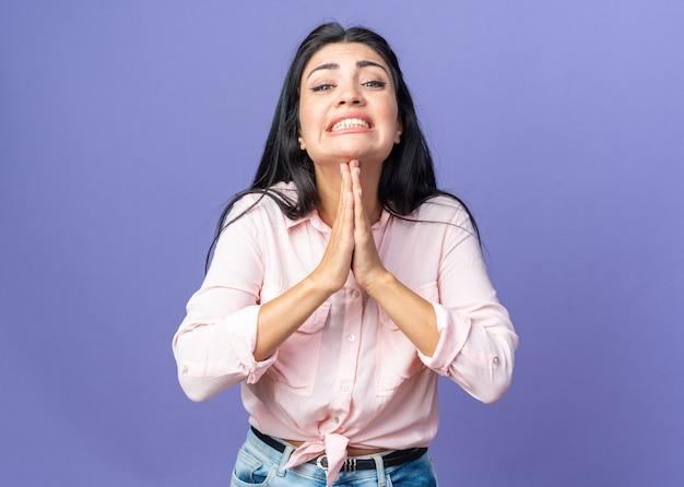 Giovane bella donna in abiti casual che si tiene per mano insieme come pregare con l'espressione di speranza che implora in piedi sul muro blu