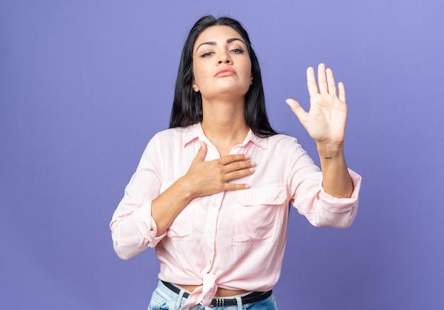 Giovane bella donna in abiti casual che fa una promessa mostrando la mano aperta e tenendo l'altra mano sul petto che sembra sicura in piedi sul muro blu
