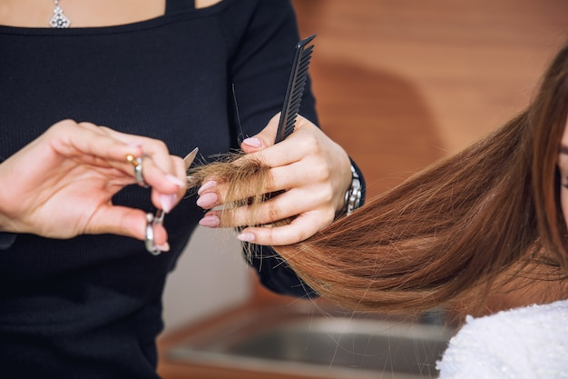 Cliente di giovane bella donna fa un taglio di capelli da un parrucchiere professionista in un primo piano del salone di bellezza