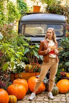 Giovane bella donna in foglie autunnali colorate e zucche