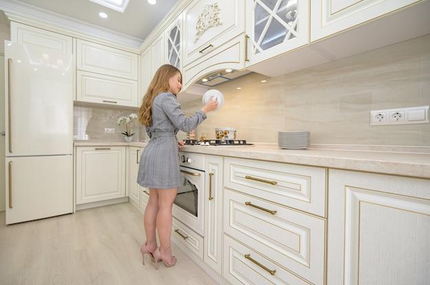Giovane bella donna che cucina alla cucina classica beige progettata in stile provenzale