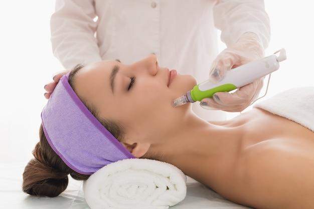 Una giovane bella donna nell'ufficio dei cosmetologi riceve una mesoterapia frazionata per il viso.