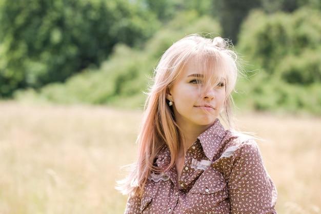 Giovane bella donna in abito stile country sul campo