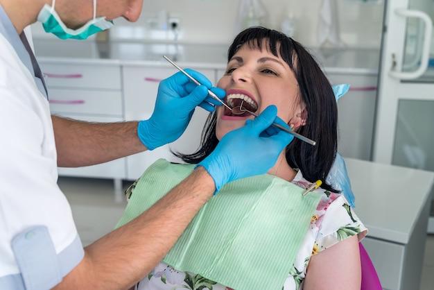 Giovane bella donna alla revisione del dentista.