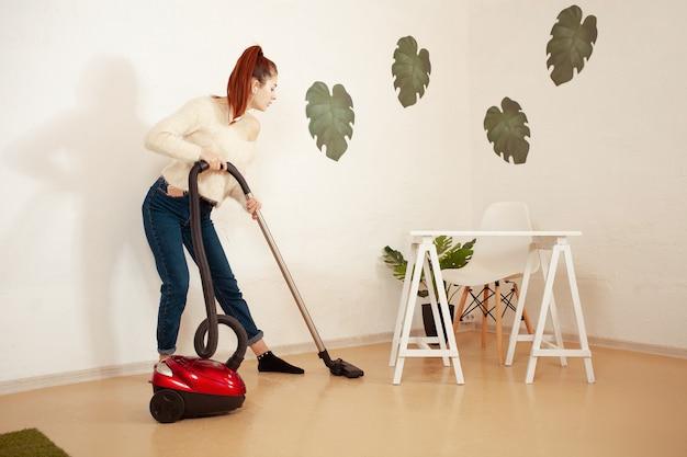 Giovane bella donna che fa le pulizie in casa