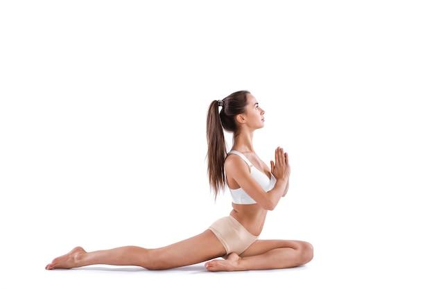 Giovane bella donna che fa pratica yoga isolata su priorità bassa bianca. concetto di vita sana. maestro di yoga.