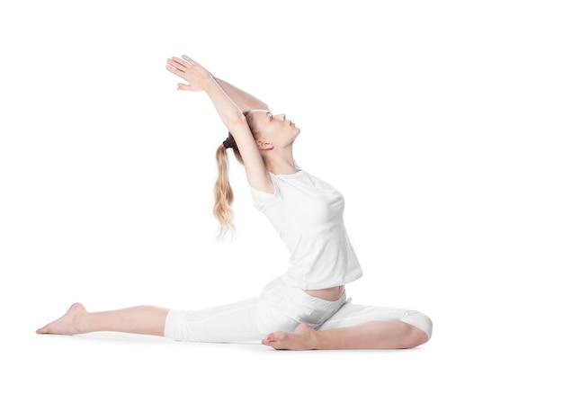 Giovane bella donna che fa yoga su bianco