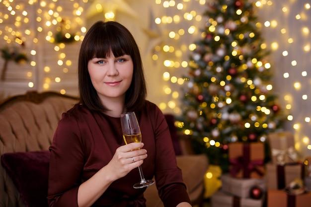 Giovane bella donna che beve champagne in un soggiorno decorato con albero di natale e luci a led per festose ghirlande