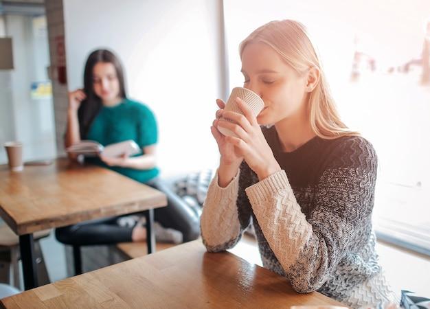 Giovane bella donna che beve caffè al bar caffetteria. modello femminile al mattino al ristorante.