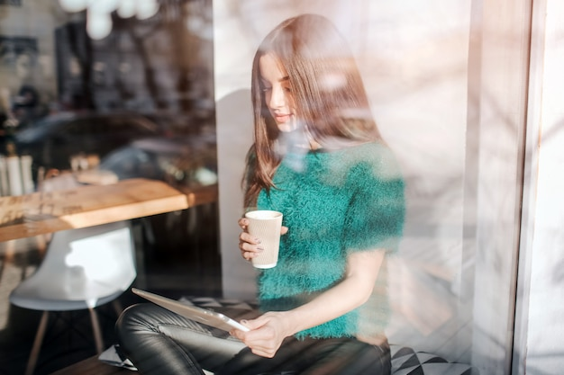 Caffè bevente della giovane bella donna al bar del caffè. modello femminile young facendo uso della compressa digitale al caffè