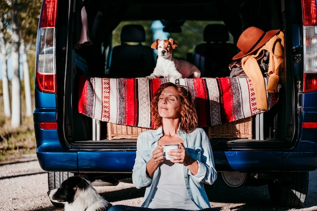 Caffè o tè bevente della giovane bella donna che si accampa all'aperto con un furgone e i suoi due cani. concetto di viaggio